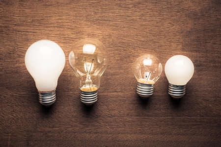 Different style and size of light bulbs in comparison concept Foto de archivo