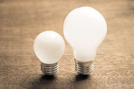 Big and small white light bulbs on wood table, productivity idea or coaching concept Stockfoto