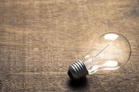 Eine Glühbirne leuchtet auf Holztisch