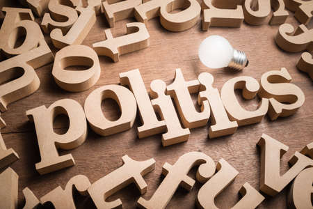 POLITICS wood word in scattered wood letters with glowing light bulb