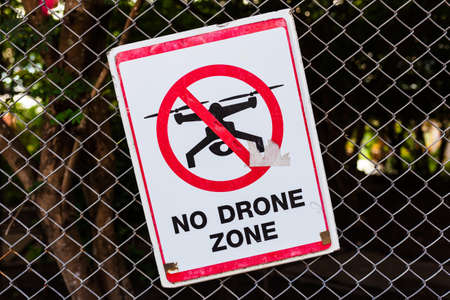 No Drone Zone, old sign on the wire mesh fence in Thai temple