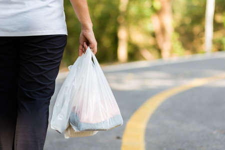 Closeup woman carry the grocery plastic bags while walking along the street, environment concept