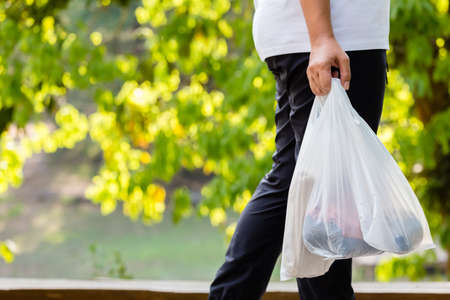 La donna del primo piano porta i sacchetti di plastica della drogheria mentre cammina nel parco della foresta, concetto dell'ambiente Archivio Fotografico