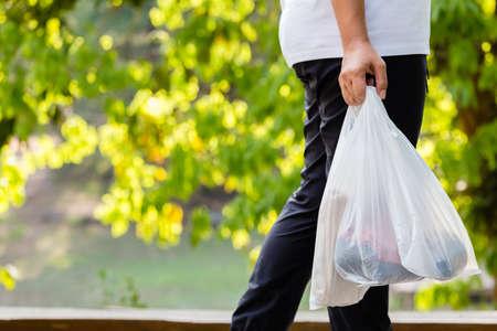 Nahaufnahmefrau trägt die Plastiktüten für Lebensmittel, während sie im Waldpark spazieren geht, Umweltkonzept Standard-Bild