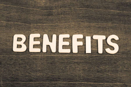 BENEFITS word by wood letters arranged on wood background Standard-Bild - 123952513