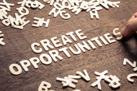 Closeup hand place the wood letters on wood table as motivation quote : CREATE OPPORTUNITIES Standard-Bild - 123952516