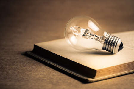 Light bulb glowing on the pages of opened old book, getting idea, reading or knowledge concept Standard-Bild - 123952518