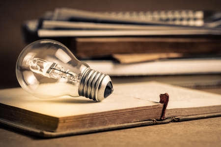 Light bulb glowing on the pages of opened old book and pile of old document on background, getting idea, reading or knowledge concept Standard-Bild - 123952519