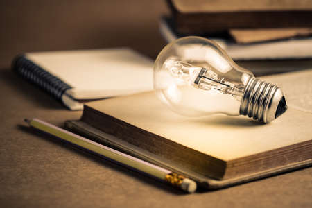 Light bulb glowing on the pages of opened old book, getting idea, reading or knowledge concept Standard-Bild - 123952520