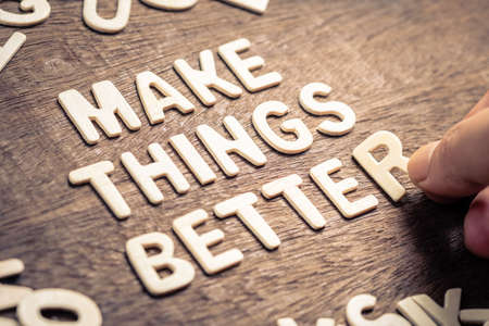 Closeup hand place the wood letters on wood table as motivation quote : MAKE THINGS BETTER