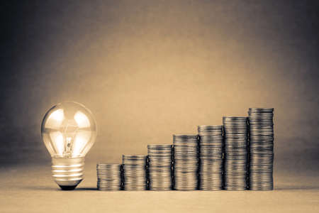 Heap coins stair and small light bulb glowing on brown background with copy space, SME or SMB, start business to success, budget or financial concept