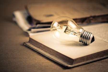 Light bulb glowing on the pages of opened old book, getting idea, reading or knowledge concept Stok Fotoğraf