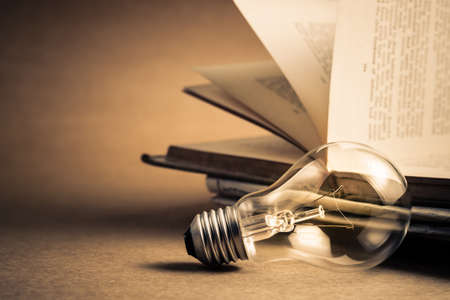 Light bulb with opened old book for reading or knowledge concept Standard-Bild - 123952553