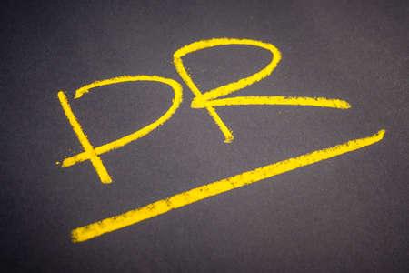 Handwriting of PR abbreviation (Public Relation) on chalkboard