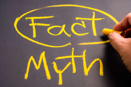 Hand write a Fact and Myth word on chalkboard Stok Fotoğraf
