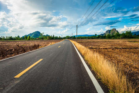 Asphalt road in the agricultural plough land, countryside of Thailand