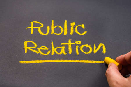 Hand writing text PUBLIC RELATION on chalkboard