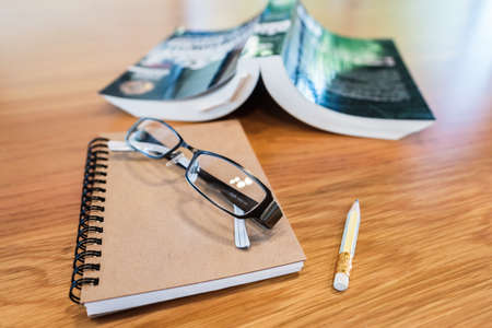 Eyeglasses on the notebook with opened book, prepare to take a short note from the book Stok Fotoğraf