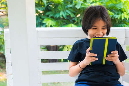 Thai child girl sit at the pavilion in the garden and enjoy watching story in the tablet Standard-Bild - 124679819