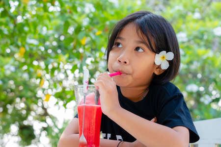 Thai child girl with plumeria flower on the ear drinking the watermelon juice in the garden