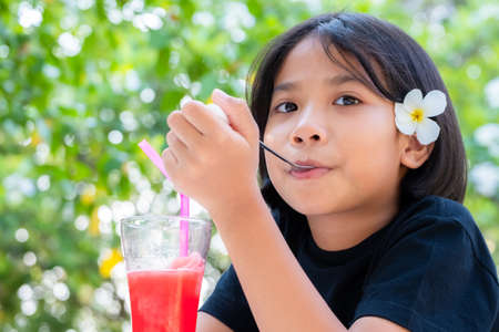 Portrait of Thai child girl with plumeria flower on the ear drinking the watermelon juice in the garden Standard-Bild - 124679821