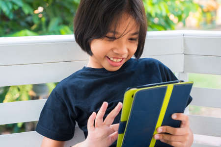 Thai child girl is enjoy while using the tablet in the garden Standard-Bild - 124679822