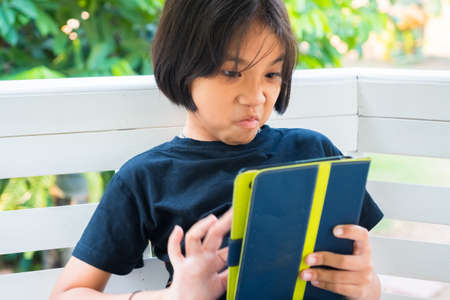 Thai child girl in angry and frustrated emotion while using the tablet in the garden Standard-Bild - 124679823