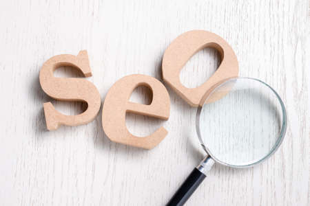 SEO (Search Engine Optimization) by wood letters with magnifying glass on wood background Stok Fotoğraf