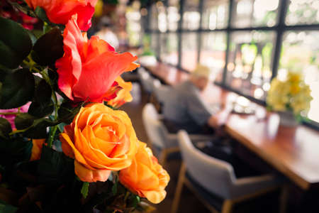 Artificial rose flowers decorated in the cafe with blurred background of customer sitting at the table by the window Standard-Bild - 124679829