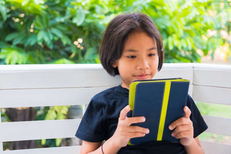Thai child girl sitting at the garden and reading tablet in her hand Standard-Bild - 124679831