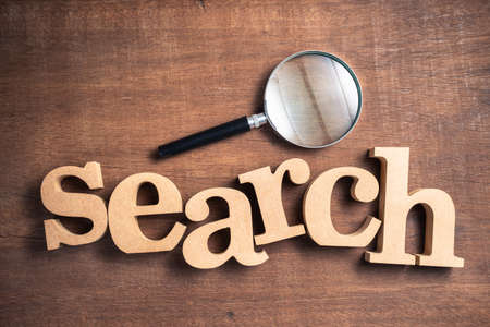 SEARCH word by wood letters with magnifying glass on wood background Stok Fotoğraf