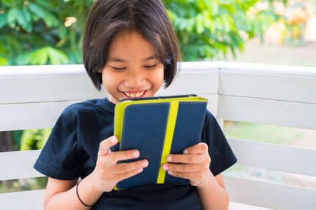 Thai child girl is enjoy and laugh while watching the story in the tablet
