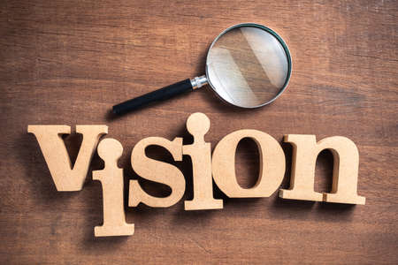 VISION word by wood letters with magnifying glass on wood background Standard-Bild - 124679836