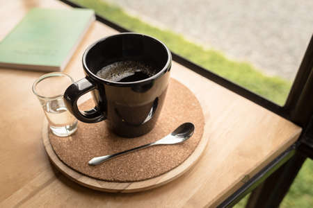Black cup of black coffee on corkboard plate with syrup, served at the table near the window with part of book on background, lifstyle relaxation Stok Fotoğraf