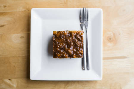 Small piece of brownie cake in white plate on wood table Standard-Bild - 124679841