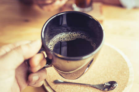 Closeup hand hold the coffee cup to drink, black drip coffee, shallow depth of field at the foam in the cup Stok Fotoğraf