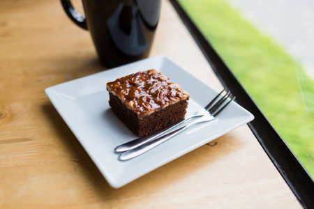 Small piece of brownie cake at the wood table near the window Stok Fotoğraf