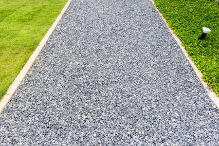 Pebbles walkway in the garden with part of lawn and green plant Standard-Bild - 124679851