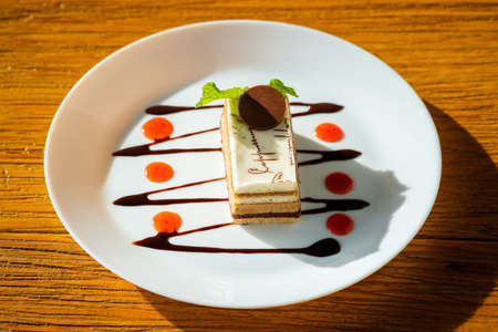 Cappuccino cake with chocolate and sauce on round white plate