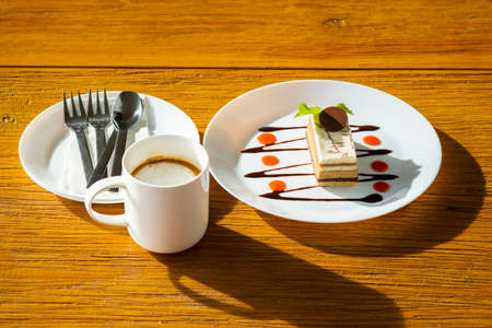 Afternoon dessert meal with cappuccino cake and cappuccino coffee set on wood table