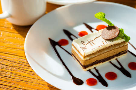 Cappuccino cake  with chocolate and sauce in round white plate Imagens