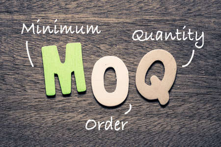 MOQ wooden alphabets on wood background with text acronym (Minimum Order Quantity)
