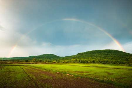 Schöner Regenbogen über der Berg- und Reisfarm, Regenzeit in der Landschaft von Thailand