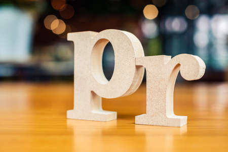 PR wood alphabet set on the table as the acronym of Public Relations, shallow depth of field to blur background