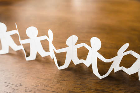 Closeup paper human chain on wood background