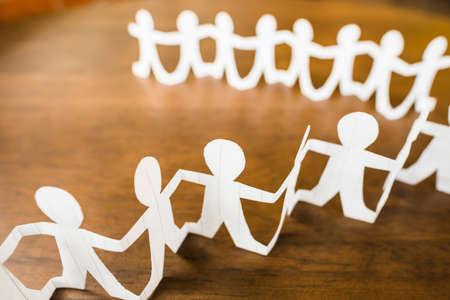Closeup row of paper human dolls as people symbol follow together