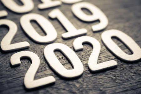 Closeup 2020 in running year numbers by wood letters on wood background