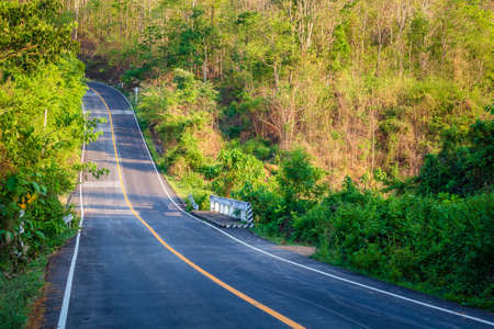 Road through the summer forest and upward to the mountain, countryside in Thailand