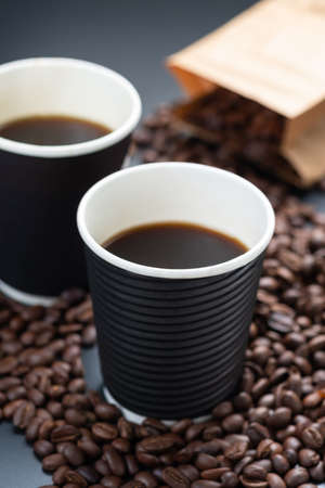 Black coffee in black biogradable cup with coffee beans and paper bag