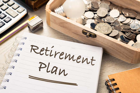 Closeup Retirement Plan text on notebook with collective coins in wood box on the desk